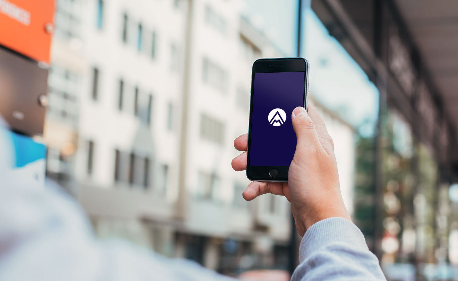 Mann mit einem Handy in der Hand, welches das Adeko-Mobile Logo zeigt
